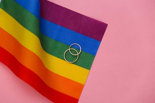 Matrimonio lgbt. bandiera arcobaleno lgbt e anelli d'oro su sfondo rosa. tolleranza, libertà