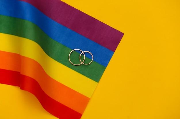 Matrimonio lgbt. bandiera arcobaleno lgbt e anelli d'oro su sfondo giallo. tolleranza, libertà