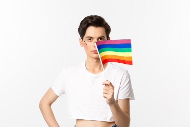 Comunità lgbtq. attraente uomo queer con svolazzi sul viso, sventolando la bandiera arcobaleno dell'orgoglio e guardando la telecamera, in piedi in top corto contro il bianco.