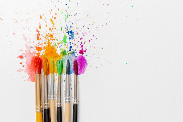 Concetto di colori lgbtq realizzato con l'aiuto di colori ad acquerello e pennelli di fiori di azalea su un foglio di carta per la pittura ad acquerello