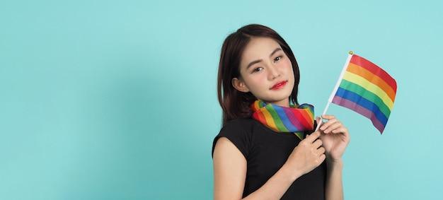Ragazza lgbtq e bandiera dell'orgoglio. ragazza lesbica sexy e bandiera lgbt in piedi. sfondo verde blu.