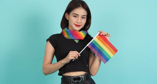 Ragazza lgbtq e bandiera dell'orgoglio. ragazza lesbica sexy e bandiera lgbtq in piedi. sfondo verde blu.