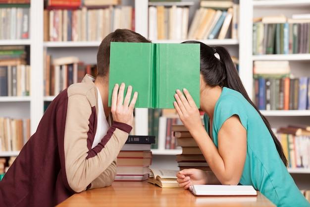 Romanzo da biblioteca. giovane uomo e donna seduti vicini al banco della biblioteca e nascondendo i loro volti dietro un libro