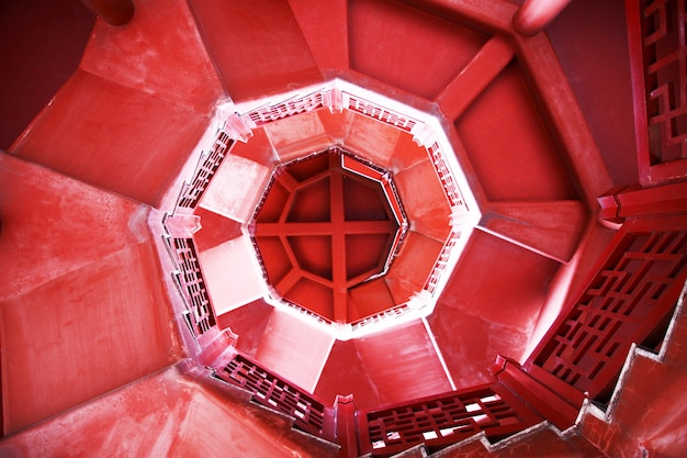 Sdraiati su una scala a chiocciola astratta da sogno con gradini in movimento e tappeto rosso