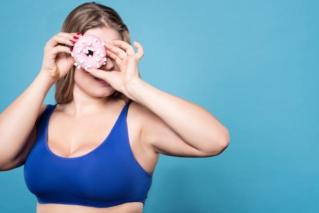 La vita diventa migliore. giovane donna in sovrappeso in piedi e guardando avanti attraverso il foro della ciambella.