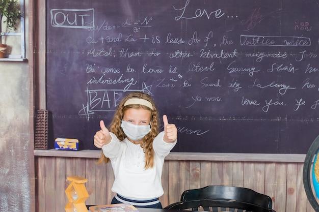 La vita durante la pandemia di coronavirus. ragazza in camicetta bianca con maschera protettiva medica che mostra i pollici in su sullo sfondo della lavagna.