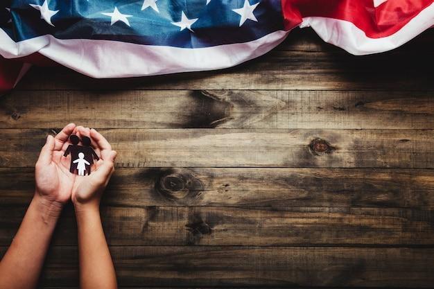 Assicurazione sulla vita, concetto di amore e famiglia - primo piano delle mani che mostrano una famiglia di carta su fondo di legno e bandiera degli stati uniti.