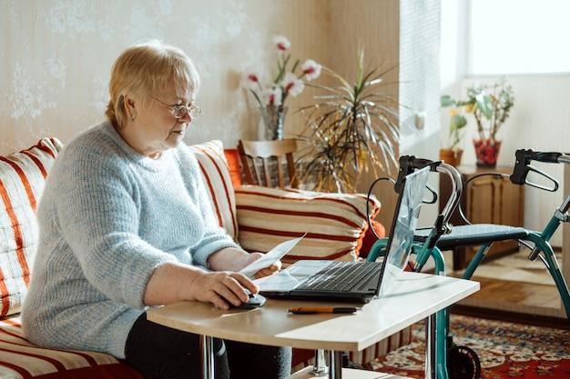 Polizza di assicurazione sulla vita per invalidità medica per anziani donna matura in bicchieri con laptop