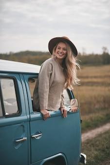 La vita è meravigliosa! attraente giovane donna sorridente sporgendosi dal finestrino del furgone mentre si gode il viaggio in macchina