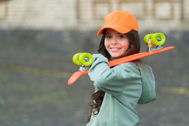 La vita è molto con lo skateboard. scheda felice del penny della tenuta della ragazza all'aperto. skateboard da strada. sport e tempo libero. trasporto e trasporto. vacanze autunnali. stile di vita attivo. dal vivo e skateboard.