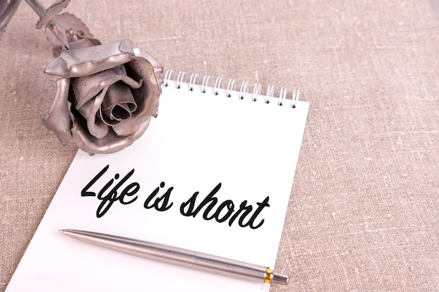 La vita è breve, il testo è scritto in un quaderno adagiato su un lino di lino e un fiore di rosa di ferro.