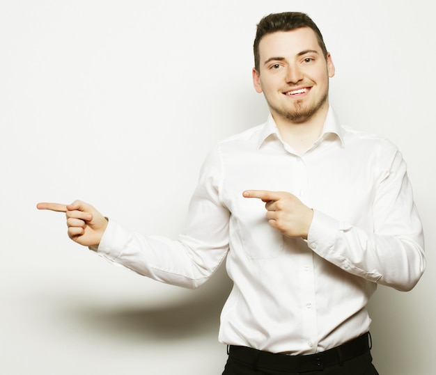 Stile di vita, affari e concetto di persone: l'uomo d'affari punta con le dita nella parte destra sopra uno spazio bianco.