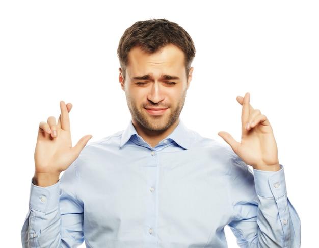 Stile di vita, affari e concetto di persone: uomo d'affari in camicia che tiene le dita incrociate mentre sta in piedi su uno sfondo bianco