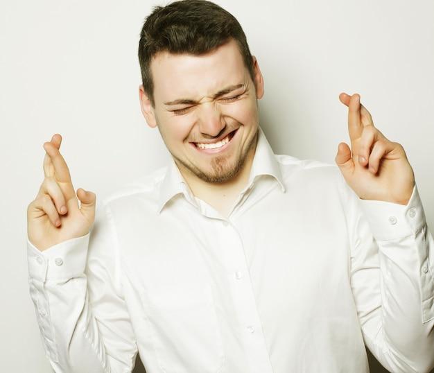 Stile di vita, affari e concetto di persone: uomo d'affari in camicia che tiene le dita incrociate mentre sta in piedi contro il bianco