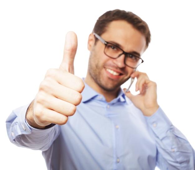 Stile di vita, affari e concetto di persone: giovane casual che mostra i pollici in su segno, mentre parla al telefono e sorride alla telecamera. isolato su sfondo bianco