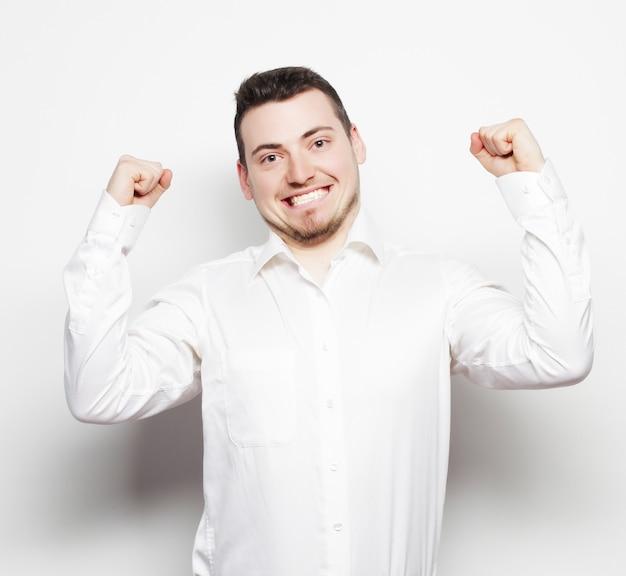 Stile di vita, affari e concetto di persone: uomo d'affari di successo. felice giovane uomo in abiti da cerimonia che gesticola e sorride mentre sta in piedi su sfondo bianco