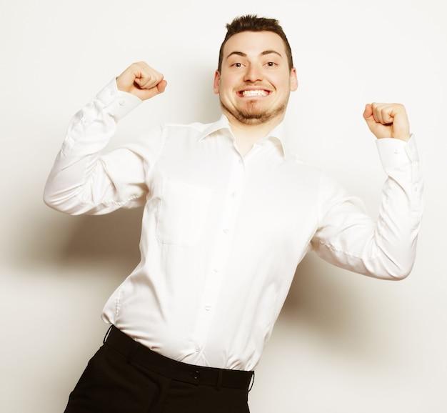 Stile di vita, affari e concetto di persone: uomo d'affari di successo. felice giovane uomo in abiti da cerimonia gesticolando e sorridente mentre in piedi su sfondo bianco