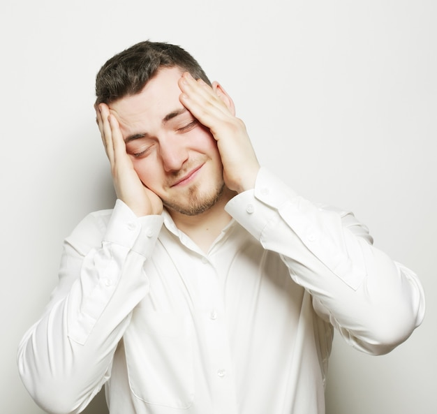 Stile di vita, affari e concetto di persone: giovane uomo d'affari con un mal di testa o un problema