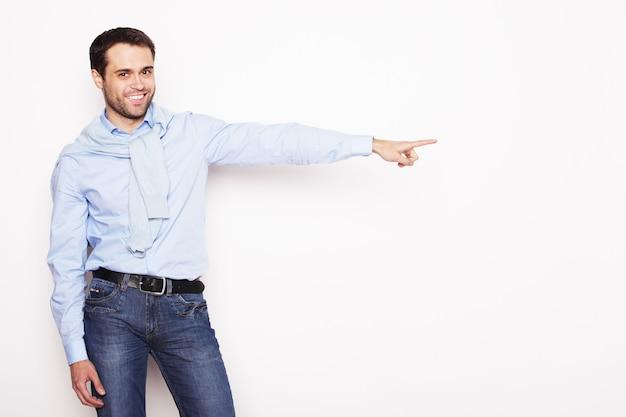 Stile di vita, affari e concetto di persone: il giovane uomo sorridente indica con le dita nella parte destra su sfondo bianco.