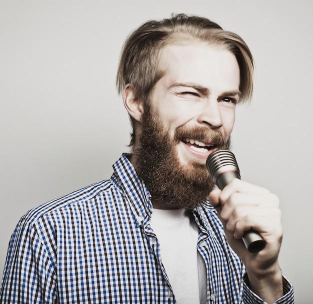 Concetto di stile di vita: un giovane con la barba che indossa una camicia bianca che tiene un microfono e canta. nello spazio grigio. foto tonificanti alla moda speciali.