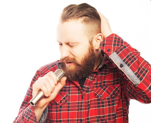 Concetto di stile di vita: un giovane con la barba che indossa una camicia bianca con in mano un microfono e canta. stile hipster. su sfondo bianco.