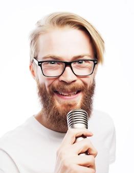 Concetto di stile di vita: un giovane con la barba che indossa una camicia bianca con in mano un microfono e canta.isolato su bianco.