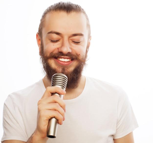 Concetto di stile di vita: un giovane con la barba che indossa una camicia bianca che tiene un microfono e canta. isolato su bianco.