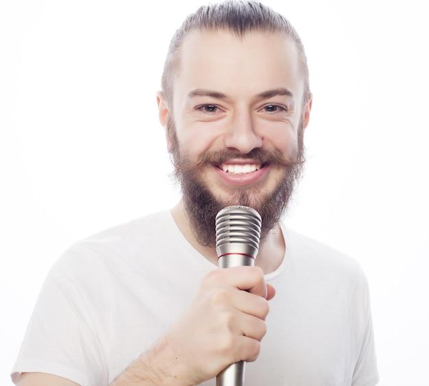 Concetto di stile di vita. un giovane con la barba che indossa una camicia bianca che tiene un microfono e canta