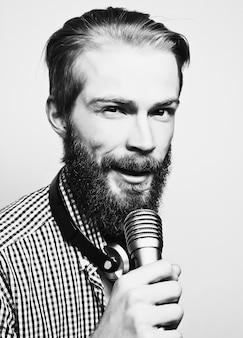 Concetto di stile di vita: un giovane con la barba che indossa una camicia bianca con in mano un microfono e canta