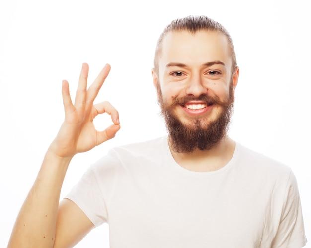 Stile di vita, educazione e concetto di persone: l'uomo felice che dà i pollici aumenta il segno - ritratto su priorità bassa bianca.