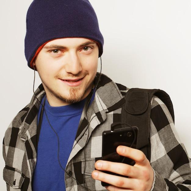 Stile di vita, educazione e concetto di persone: giovane che ascolta musica e utilizza lo smartphone, mentre si trova su uno sfondo grigio.