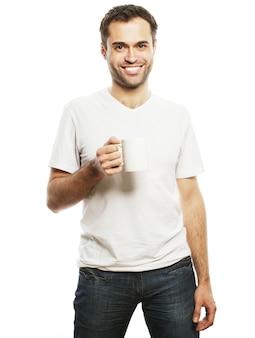 Stile di vita, cibo e concetto di persone: giovane casual che tiene una tazza bianca con caffè o tè.