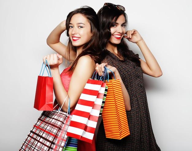 Stile di vita, felicità, emozioni e concetto di persone: belle ragazze adolescenti che trasportano borse della spesa, su bianco