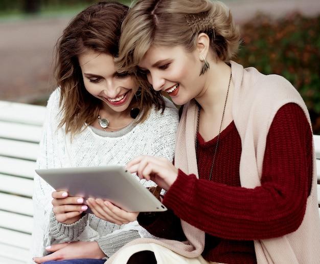 Stile di vita, felicità, emozioni e concetto di persone: belle donne ragazze autunno utilizzando tablet all'aperto