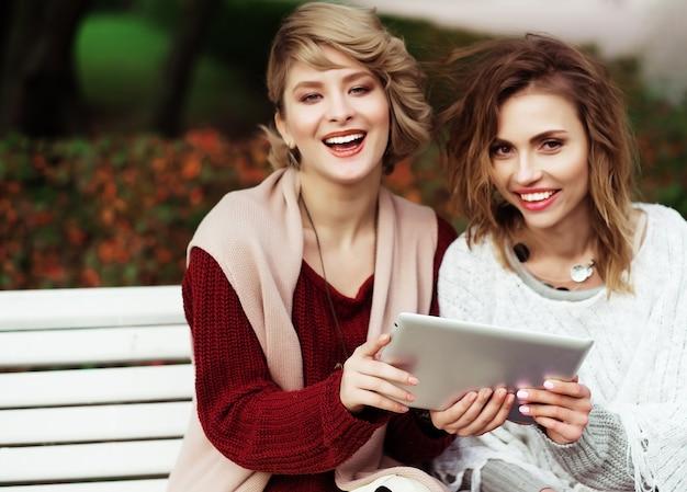 Stile di vita, felicità, concetto emotivo e di persone: belle donne ragazze autunno utilizzando tablet all'aperto