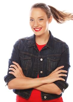 Stile di vita, felicità, emozioni e concetto di persone: bella giovane donna che indossa una camicia rossa che guarda la telecamera e fa emozioni diverse su sfondo bianco