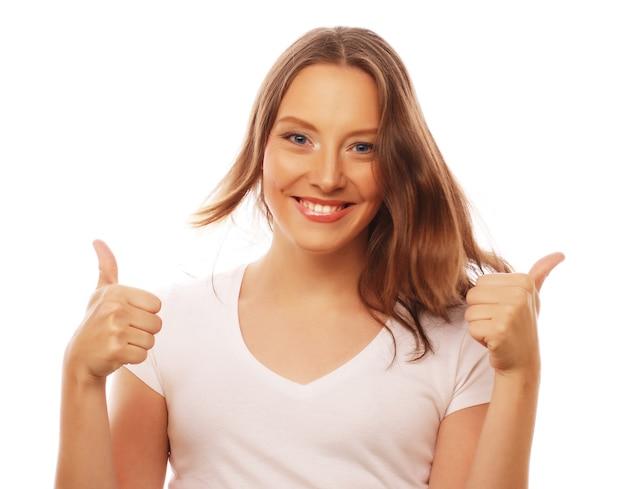 Stile di vita, felicità, emozioni e concetto di persone: bella giovane donna che indossa una camicia bianca che guarda l'obbiettivo e fa emozioni diverse stando in piedi su sfondo bianco