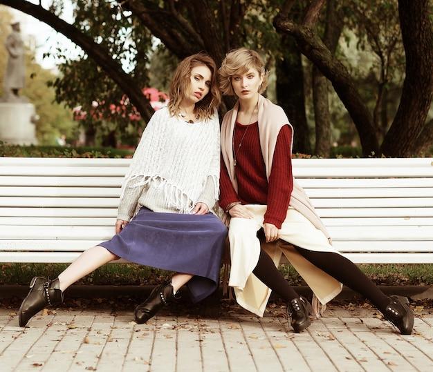 Stile di vita, felicità, emozioni e concetto di persone: belle giovani donne sedute su una panchina nel parco autunnale