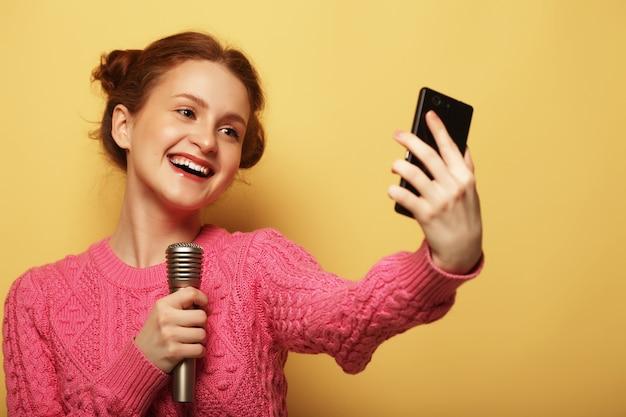 Stile di vita, felicità, emotività e concetto di persone. ragazza di bellezza con un microfono che canta e scatta selfie