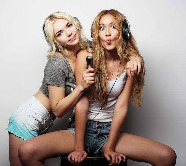 Stile di vita, felicità, emozioni e concetto di persone: ragazze hipster di bellezza con un microfono che cantano e si divertono