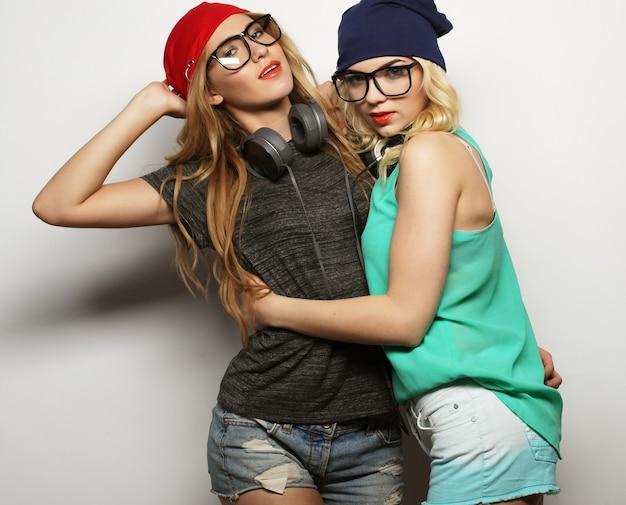 Stile di vita, felicità, emozioni e concetto di persone: primo piano ritratto di stile di vita alla moda di due giovani ragazze hipster migliori amiche, che indossano un trucco luminoso e cappelli alla moda simili, fanno facce buffe