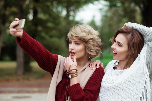 Stile di vita, felicità, emotivo e concetto di persone: amici che fanno selfie. due belle giovani donne che fanno selfie nella sosta di autunno.