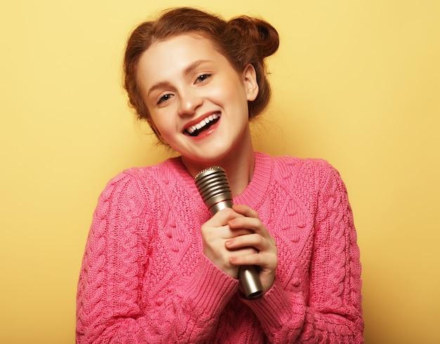 Stile di vita, felicità, emotività e concetto di persone. ragazza con un microfono che canta e si diverte