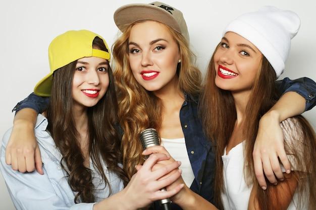 Stile di vita, felicità, emozioni e concetto di persone: gruppo di giovani donne che si divertono al karaoke