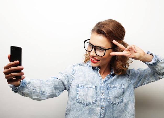 Stile di vita, felicità, emozioni e concetto di persone: ragazza graziosa hipster che prende selfie.