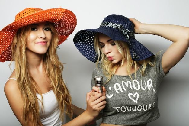 Stile di vita, felicità, emozioni e concetto di persone: due ragazze di bellezza con un microfono che cantano e si divertono