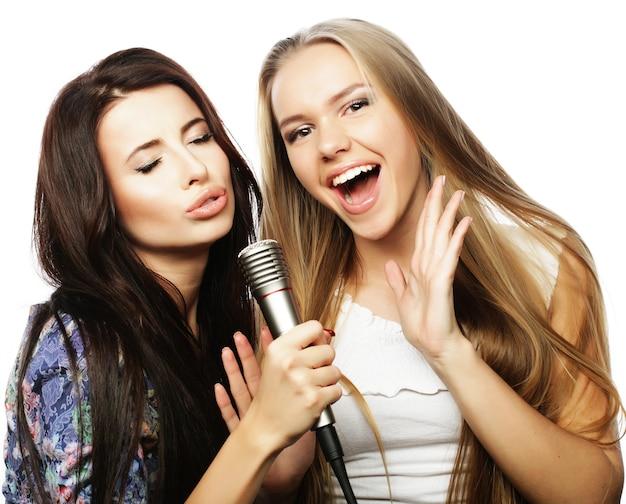 Stile di vita, felicità, emozioni e concetto di persone: due ragazze hipster di bellezza con un microfono che cantano e si divertono