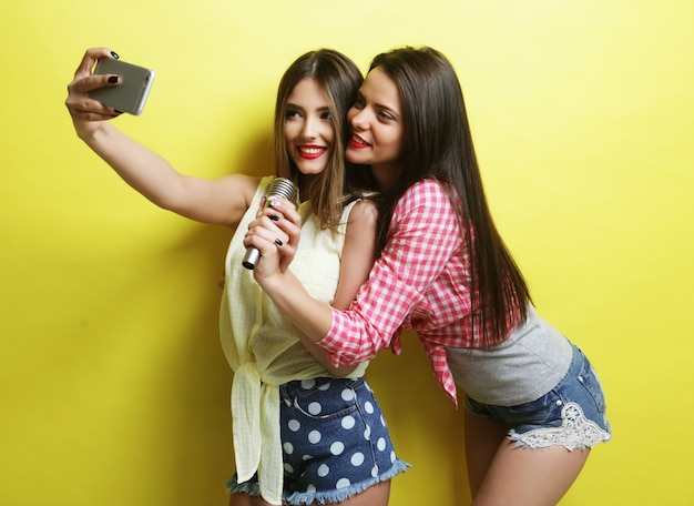 Stile di vita, felicità, emozioni e concetto di persone: due ragazze hipster di bellezza con un microfono si fanno selfie su sfondo giallo