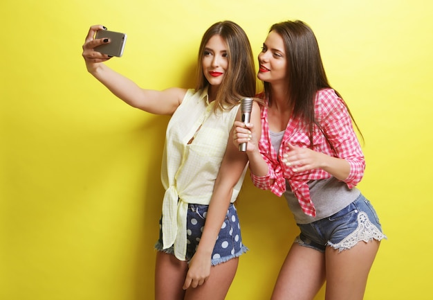 Stile di vita, felicità, emotività e concetto di persone: due ragazze hipster di bellezza con un microfono prendono selfie