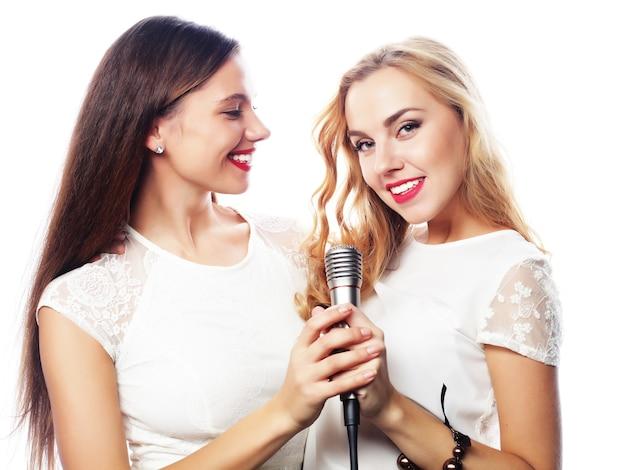 Stile di vita, felicità, concetto emotivo e di persone: due ragazze che cantano, su sfondo bianco white